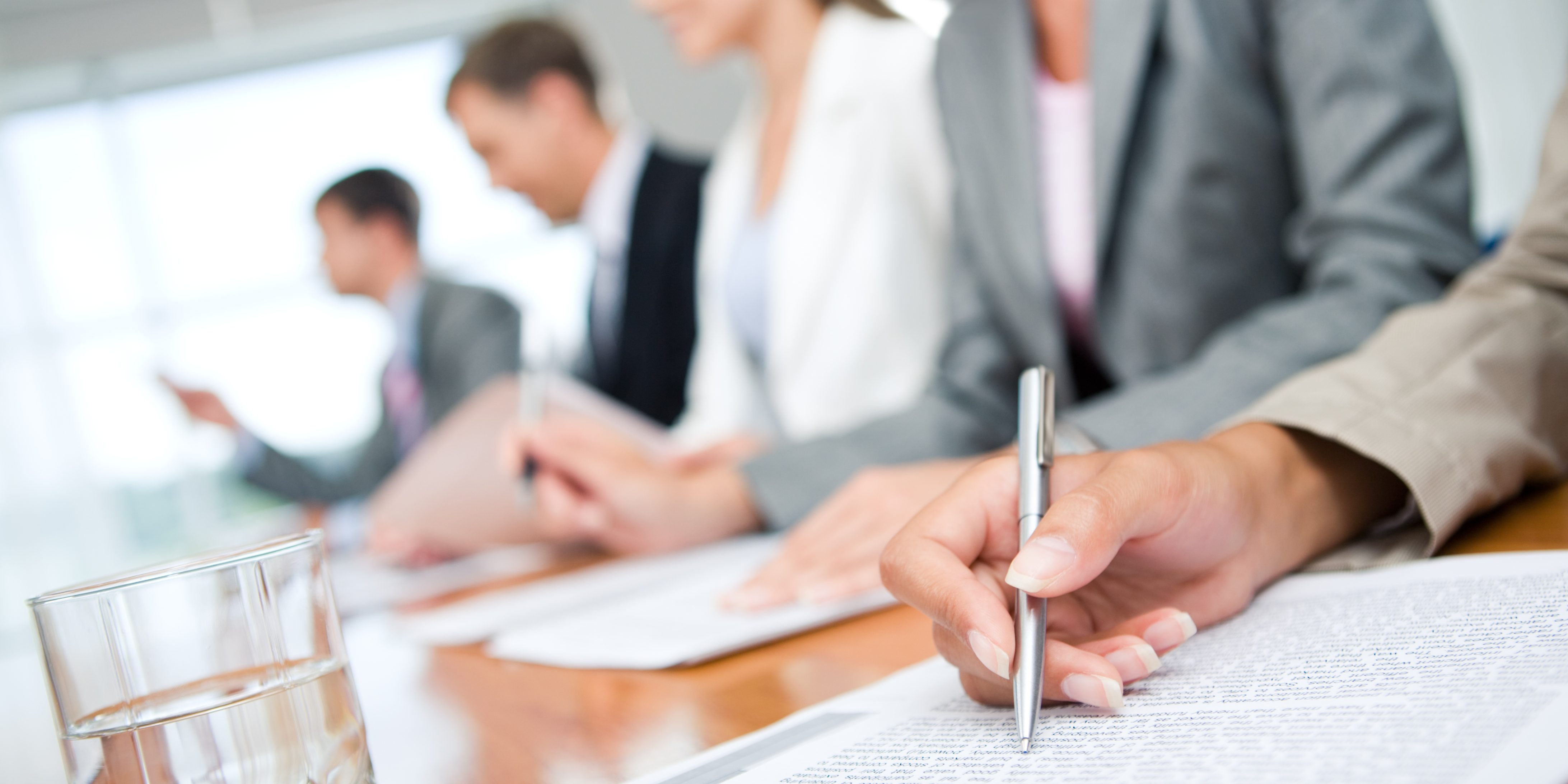 Close-up of woman's hand with pen over document on background of business group